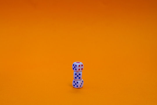 Close-up Of Stacked Dices Against Orange Background