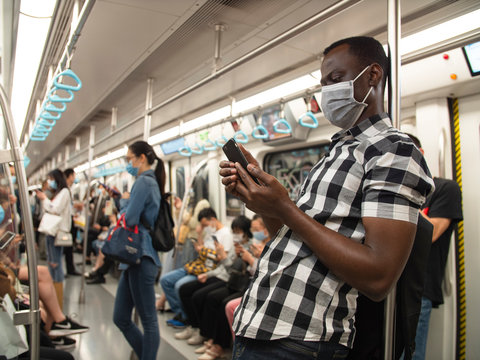 Close up of one black man wear mask in the subway using mobile phone passengers in the train all with mask people wear mask in public transport during pandemic of coronavirus Covid-19