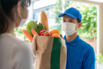 Asian delivery man wearing face mask and glove with groceries bag of food, fruit, vegetable give to woman costumer in front of the house during time of home isolation.