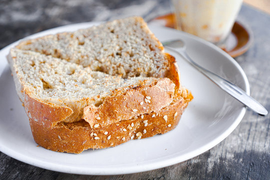slice of bread with sunflower seeds and milk for breakfast on the white plate and fork
