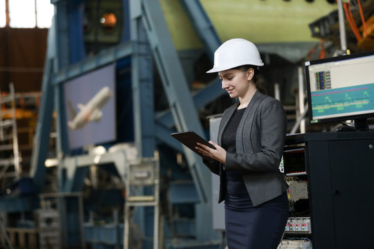 Portrait of a female factory manager in a white hard hat and business suit. Controlling the work process at the airplane manufacturer.
