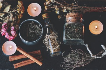 Flat lay of kitchen witchery using herbs and spices found at home. Herbal magick in wicca and witchcraft. Glass jars filled with dried herbs and spices, cinnamon, flowers, camomile, burning candles