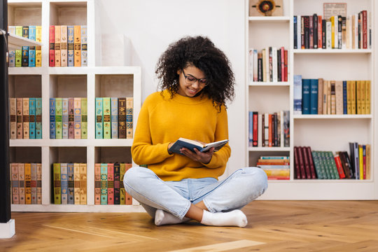 Image of joyful african american woman reading book while sitting