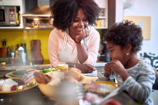 mother and daughter at dining table, talking, smiling. Family togetherness concept