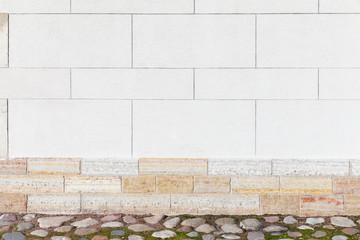 Fototapete - White stone wall with cobblestone ground