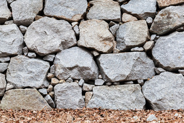 Fototapete - Old wall made of rough gray stones and dry leaves