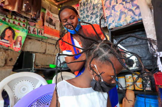 """Stacy Ayuma gets plaited with the """"coronavirus"""" hairstyle, designed to emulate the prickly appearance of the virus under a microscope as a fashion statement against the spread of the coronavirus disease (COVID-19) in Kibera, Nairobi"""