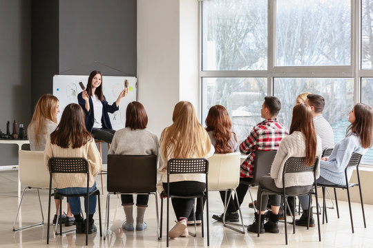 Professional hairdresser teaching young people in office