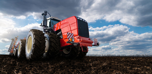 Etiqueta Engomada - Red tractor with plow on a agricultural field