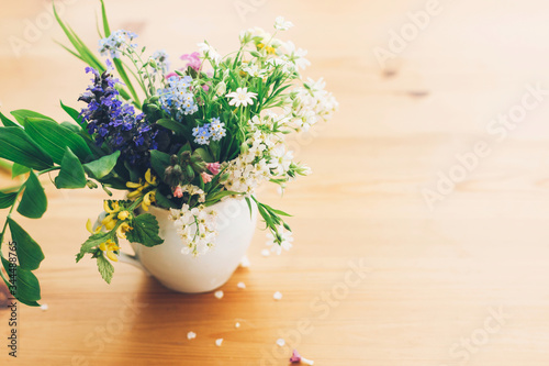Wildflowers bouquet in old cup on wooden table,  space for text. Blooming spring flowers in soft light, rural still life. Happy  Mother's day. Hello spring.
