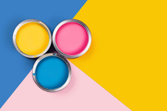 Repare concept. Tricolor blue, yellow, pink background with three colors paint cans. Flat lay, top view, copy space.