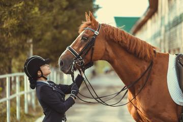 Foto op Plexiglas horsewoman jockey in uniform standing with black horse outdoors