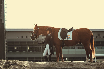 Beautiful professional female jockey standing near horse. woman horse rider is preparing to equitation. girl and horse. equestrian sport concept. dressage horse  Papier Peint