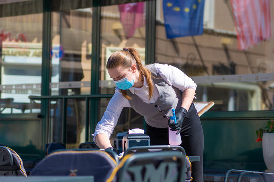 Waitress with a mask disinfects the table of an outdoor bar, café or restaurant, reopen after quarantine restrictions