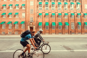 Two bicyclists driving past historical facade of ancient Scandinavian city without walking people