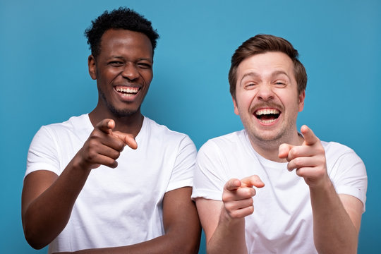 Two man african american and caucasian pointing at camera with index finger and laughing out loud