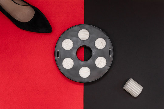 3D printing filament reel for 3d printers, and the printed part of a greek column and shoe are on a black, red background. The concept of the future printing shoes and accessories at home.