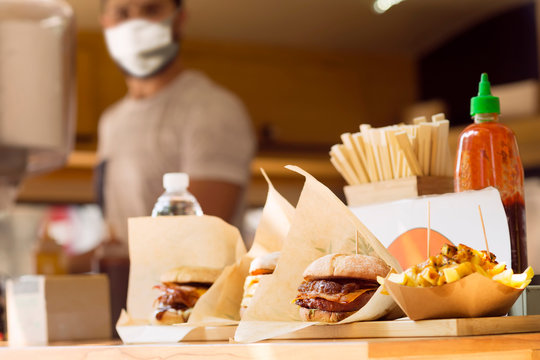 chef with mask for coronavirus prevention on food truck , selective focus in foreground