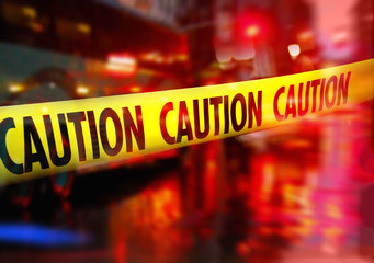 Crime scene caution tape and blurred law enforcement  background