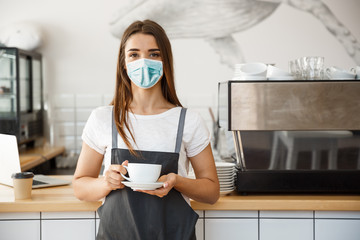 Photo sur Aluminium Cafe Business Owner Concept - Beautiful Caucasian Barista in face mask offers hot coffee at the modern coffee shop