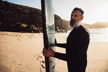 senior man with long beard carrying surfboard at beach