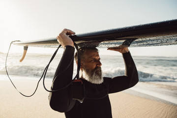 Caucasian Senior man with beard carrying surfboard on his head