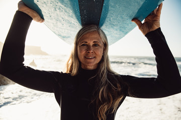 Portrait of smiling senior woman carrying surfboard on beach