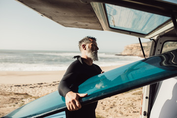 Senior man taking out surfboard from van on beach