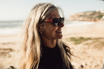 Smiling senior woman wearing sunglasses standing on beach