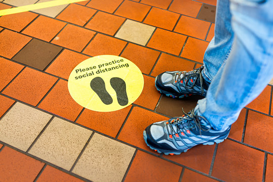 Yellow warning sign to maintain social distance distancing during covid-19 coronavirus outbreak with footsteps in store and legs of person in USA