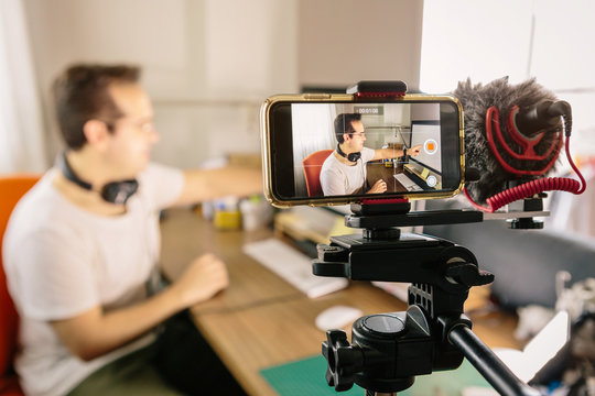 Boy recording with his mobile phone a video for social networks. Use an external microphone to make it easier to hear. Youtuber