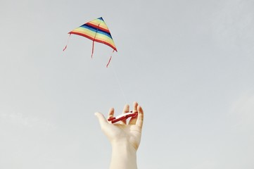 Cropped Image Of Woman Flying Kite Against Clear Sky