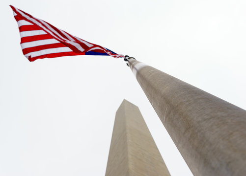 Low Angle View Of American Flag By Monument Against Clear Sky