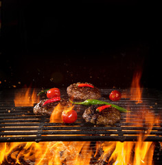 Tasty beef burger steaks on the grill with fire flames