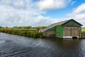 A roughly constructed green corrugated iron boat house on the little ringsloot, in Warmond in the Netherlands.