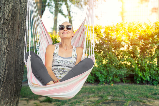 Young adult happy short haired shaved bald attractive woman chilling enjoy relaxing sitting in fabric chair hammock at yard in garen near house. Peaceful and idyllic outdoor rest lifestyle