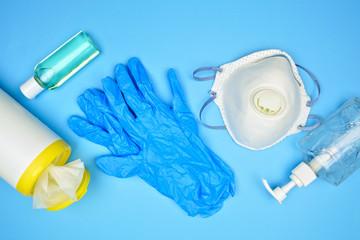 Coronavirus prevention equipment, sanitizing wipes, hand sanitizer, gloves, n95 mask. Top view set on a blue background.