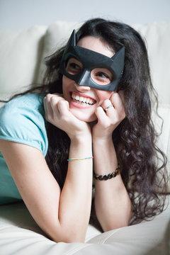 Cheerful Young Woman Wearing Batman Mask