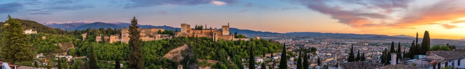 The palace of Charles V in Granada from the viewpoint of San Nicolas. Panoramic view of the Alhambra with Sierra Nevada and Granada in the background, incredible sunset. Fototapete