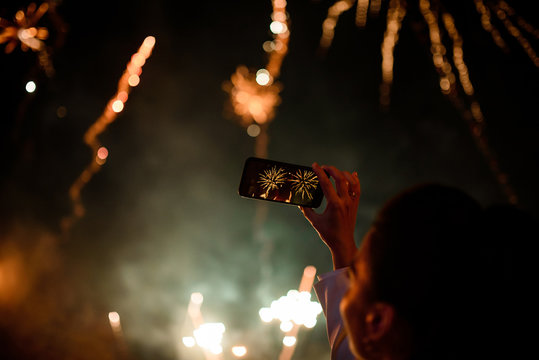 Hand of woman taking the photo to fireworks with the new smartphone.