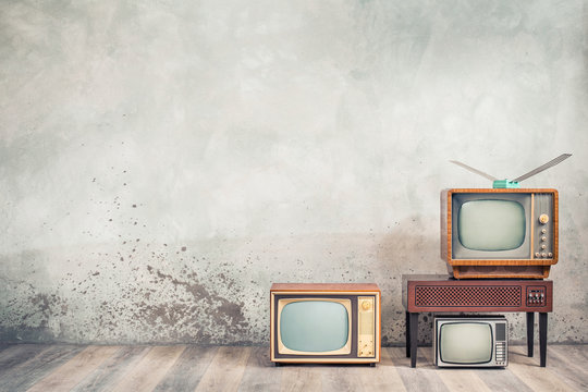 Retro cathode ray tube (CRT) monochrome television sets and classic wooden TV stand with outdated amplifier front concrete wall background. Broadcasting, news concept. Vintage old style filtered photo