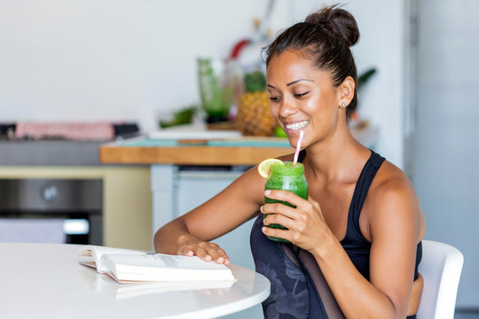 Latin woman staying healthy at home having a green juice