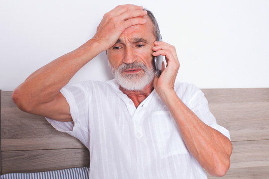 Sick elderly man calling a doctor