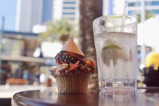 Close-up Of Cupcake With Lemonade On Table At Sidewalk Cafe