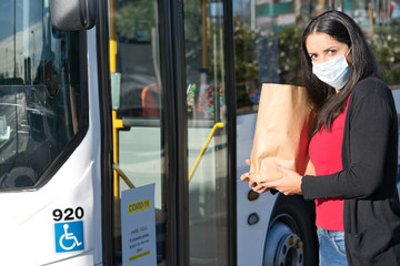 Hispanic woman holding shopping bag and wearing face mask against coronovarius at the bus stop