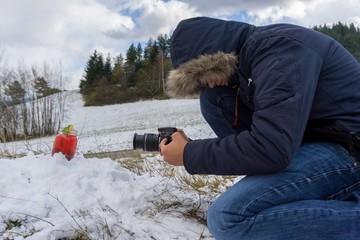 Man taking photos of lemonade on snow in winter