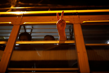 A Guatemalan migrant gestures a victory sign from inside a bus while arriving to a hotel with other deportees from the U.S., in Guatemala City