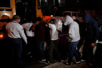 Guatemalan migrants board a bus after being deported from the U.S. outside Guatemala's Air Force base in Guatemala City