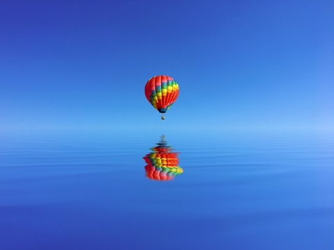 Reflection Of Colorful Hot Air Balloon On Water