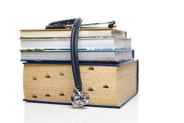 Medical professional education concept. A stethoscope draped over a stack of medical books, isolated on white.